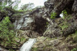 Водопад вытекает из карстового моста и имеет три ступени, каждая из них выше человека минимум в два раза